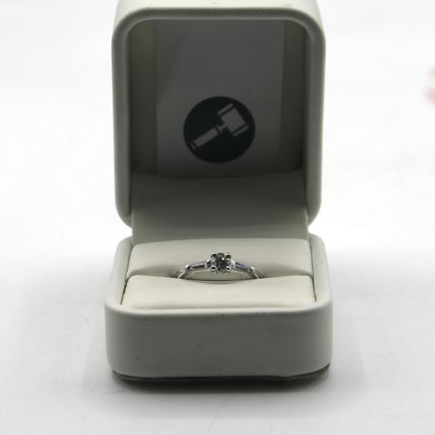 Lot 10 DESIGNER PLATINUM SOLITAIRE RING SET WITH A DIAMOND TO CENTRE & A BAGUETTE TO EACH SHOULDER
